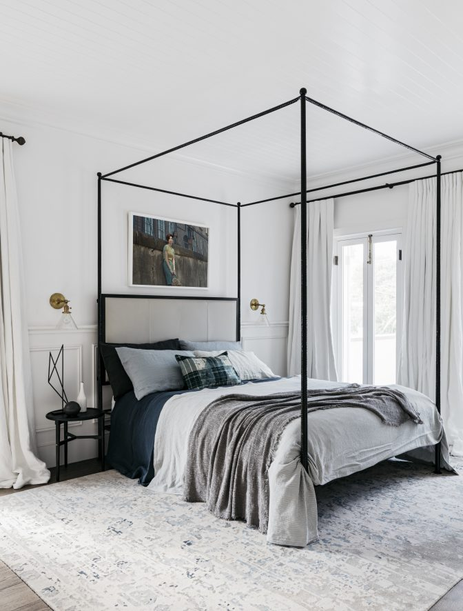 Guest bedroom with four poster bed features in this beach side vacation home by Alexander &CO.