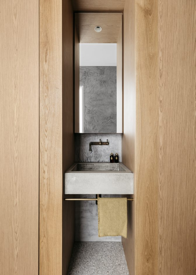 Timber joinery envelopes a custom-concrete sink and brass hardware in this home for a young professional family.
