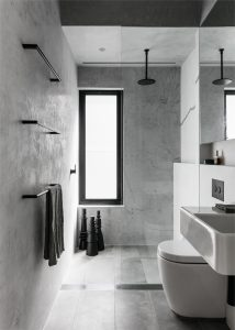 Polished plaster walls and stone floor tile are defined by blackened metal hardware in this urban Sydney bathroom.