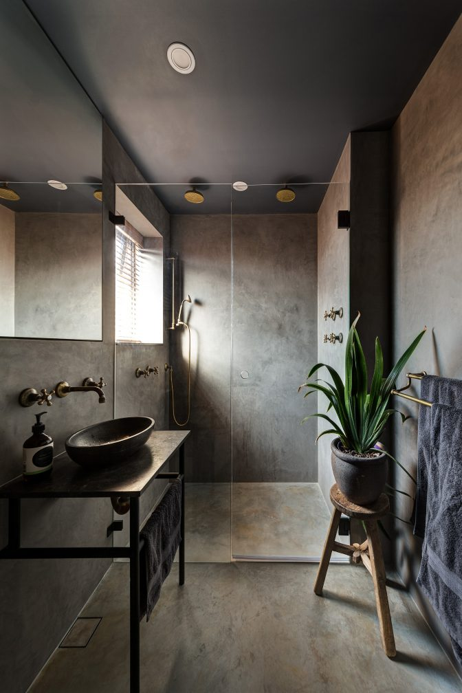In this Penthouse apartment, a dark, moody bathroom scheme features polished plaster wall treatment and brass hardware.