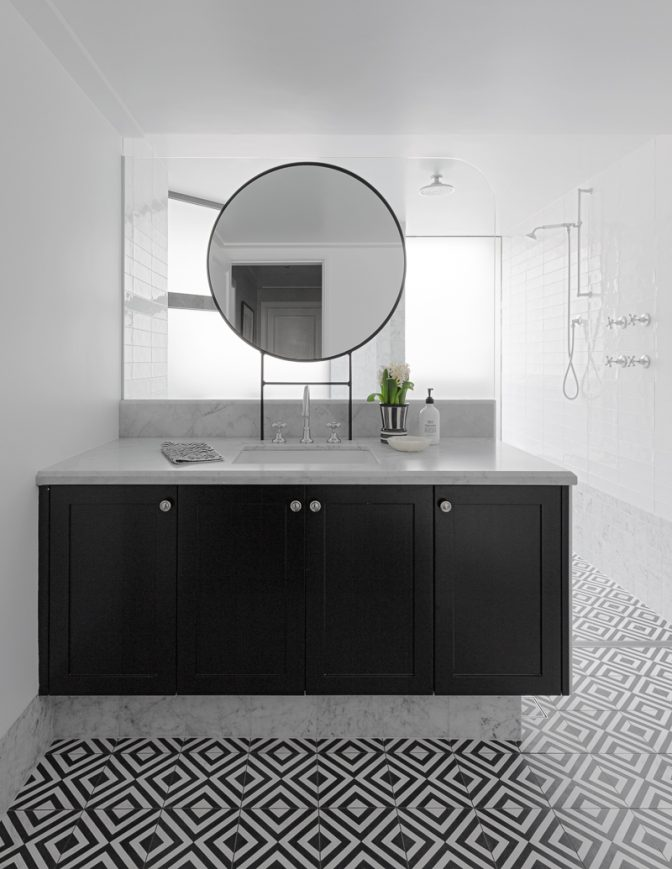 In Sydney's Elizabeth Bay, a monochromatic bathroom scheme features carrara marble, geometric floor tiles and a custom vanity with painted timber joinery